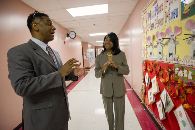 Principal and coach in hallway